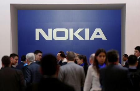 FILE PHOTO - Visitors stand next to a logo of Nokia at Mobile World Congress in Barcelona