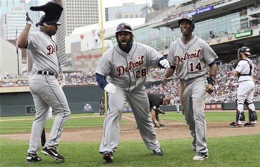 Detroit Tigers' Prince Fielder, center, celerbates with Delmon Young, left, and Austin Jackson after Fielder's two-run home run off Minnesota Twins pitcher Jared Burton in the eighth inning of a baseball game Sunday, Sept. 30, 2012 in Minneapolis. The Tigers won 2-1. (AP Photo/Jim Mone)