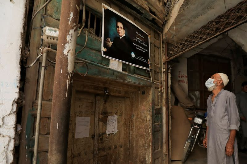 A man reads a sign on a closed entrance of childhood home of Bollywood actor Mohammad Yusuf Khan, popularly known as Dilip Kumar, in Peshawar