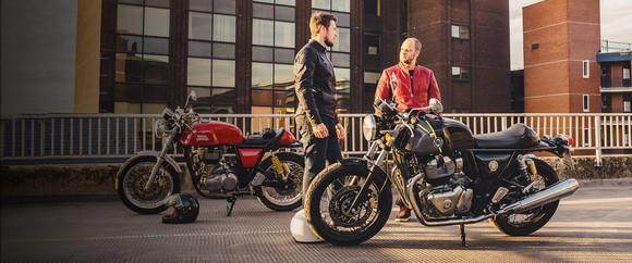 Two men standing by two motorcycles