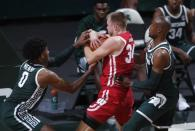 Michigan State's Aaron Henry, left, and Joshua Langford, right, pressure Wisconsin's Brad Davison, center, during the second half of an NCAA college basketball game, Friday, Dec. 25, 2020, in East Lansing, Mich. Wisconsin won 85-76. (AP Photo/Al Goldis)