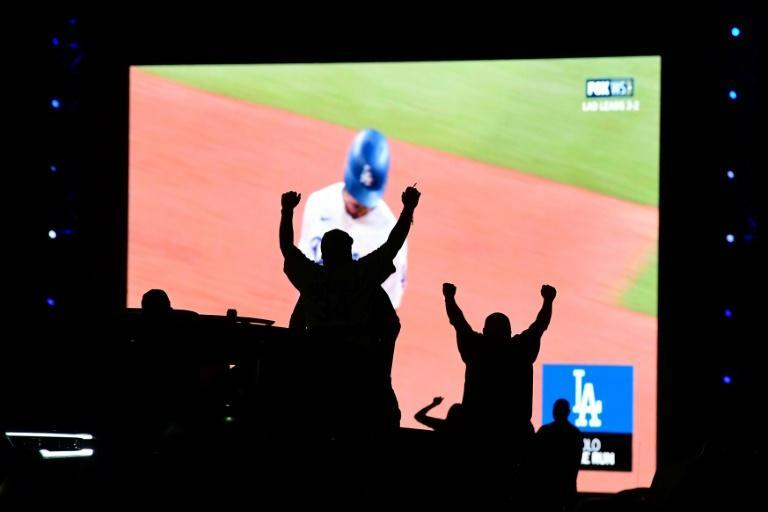 Dodgers fans watch their team's World Series-clinching win over Tampa Bay on big screens set up in the Dodger Stadium parking lot to show the game played in a quarantine bubble in Texas