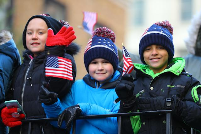 <p>Children wave flags while riding a float during the Veterans Day parade in New York City on Nov. 11, 2017. (Photo: Gordon Donovan/Yahoo News) </p>