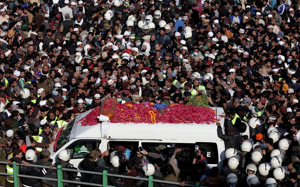 People chant slogans as they gather near an ambulance carrying the body of Khadim Hussain Rizvi - Reuters