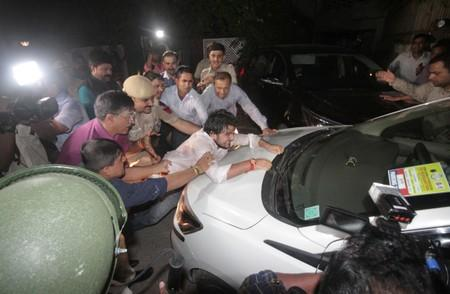 Supporter of India's former Finance Minister Chidambaram tries to stop a vehicle carrying Chidambaram after he was arrested by CBI officials in New Delhi