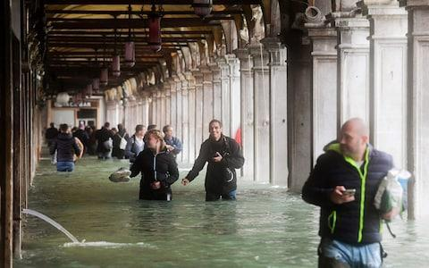 Tourists wade under arches next to the flooded St Mark's Square - Credit: AFP