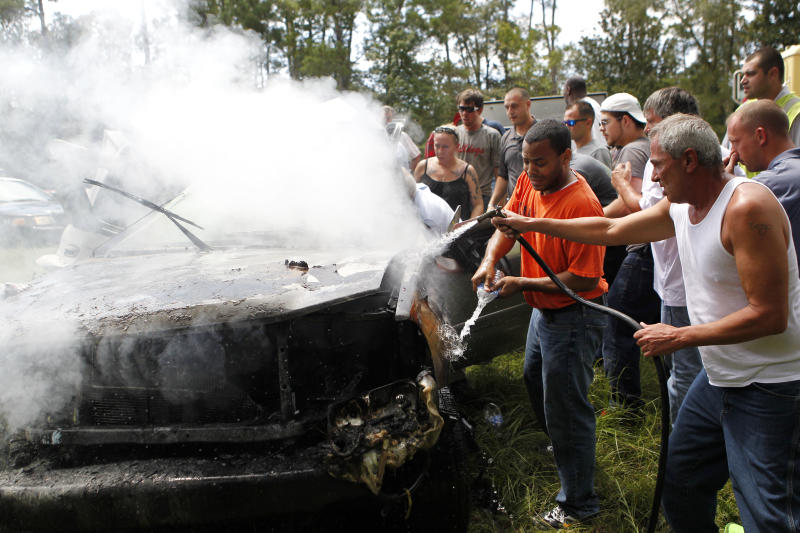 CORRECTS THAT DISABLED WOMAN IS THE DRIVER'S SISTER, NOT HER CHILD -  Passers-by use a hose from a cement mixer and bottles of spring water to douse the fire as they rescue a woman pinned in a burning car on Interstate 10 in Hancock County, Miss., Thursday, Aug. 16, 2012. The fire was extinguished by the hose of a cement mixer, and fire extinguishers from nearby truckers. The woman was then extracted from the wreckage by the civilians as rescue personnel arrived, and she and her disabled sister, who was removed from the wreckage early, were airlifted from the scene. (AP Photo/Gerald Herbert)