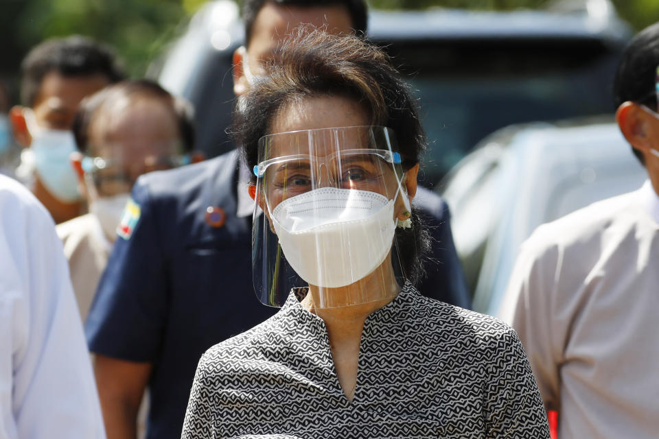 Myanmar leader Aung San Suu Kyi wearing a protective face mask and shield walks to greet supporters as she leaves after a demonstration of the voting for the upcoming Nov. 8 general elections, Tuesday, Oct. 20, 2020, in Naypyitaw, Myanmar. (AP Photo/Aung Shine Oo)
