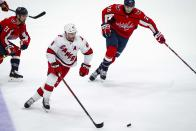 Carolina Hurricanes left wing Jordan Martinook (48), from Canada, skates with the puck as Washington Capitals right wing Garnet Hathaway (21) and center Nic Dowd (26) defend during the first period of an NHL hockey game, on Monday, Jan. 13, 2020, in Washington. (AP Photo/Al Drago)