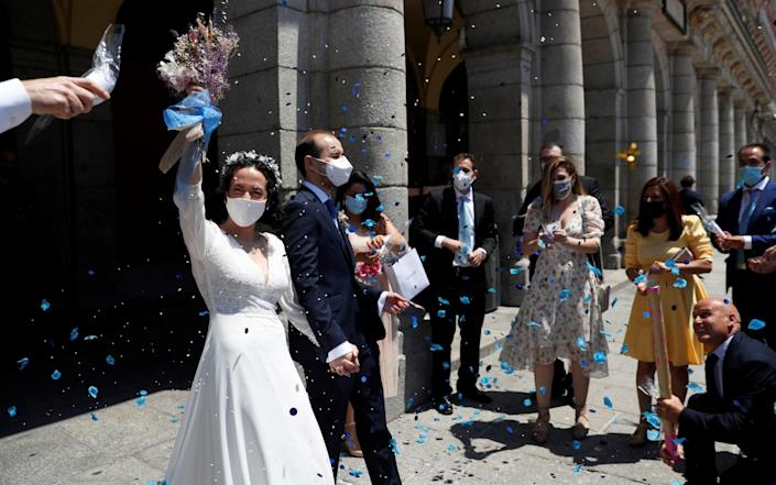 Newlyweds and their wedding party keep their protective masks on - SUSANA VERA/REUTERS