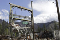 A road sign is seen through a melted gas station placard in Blue River, Ore., on May 17, 2021. Blue River, an unincorporated community along the McKenzie River east of Eugene, Oregon, was one of many places in western Oregon devastated last fall during a 72-hour firestorm. Oregon's unprecedented 2020 wildfire burned 4,000 homes and more than 1 million acres, many of them in rainy areas of the state that aren't normally associated with extreme wildfire. (AP Photo/Gillian Flaccus)