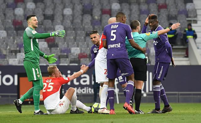 Soccer Football - Ligue 1 - Toulouse vs AS Monaco - Stadium Municipal de Toulouse, Toulouse, France - February 24, 2018 Monaco's Kamil Glik is pulled to his feet as referee Benoit Millot awards a free kick REUTERS/Fred Lancelot