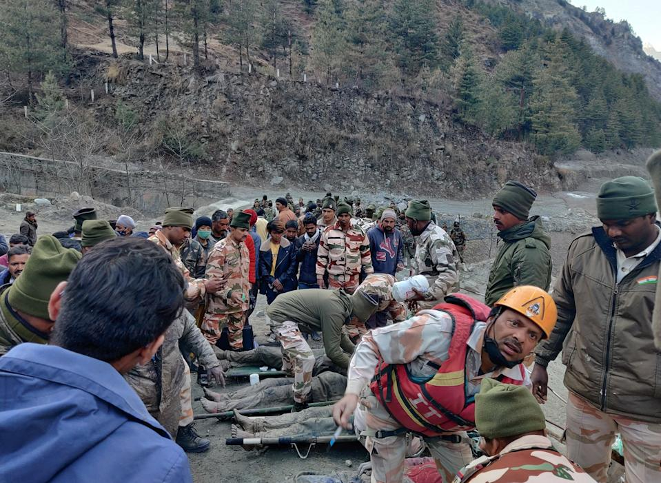 <p>Members of Indo-Tibetan Border Police tend to people rescued after a Himalayan glacier broke and swept away a small hydroelectric dam, in northern India</p> (REUTERS)