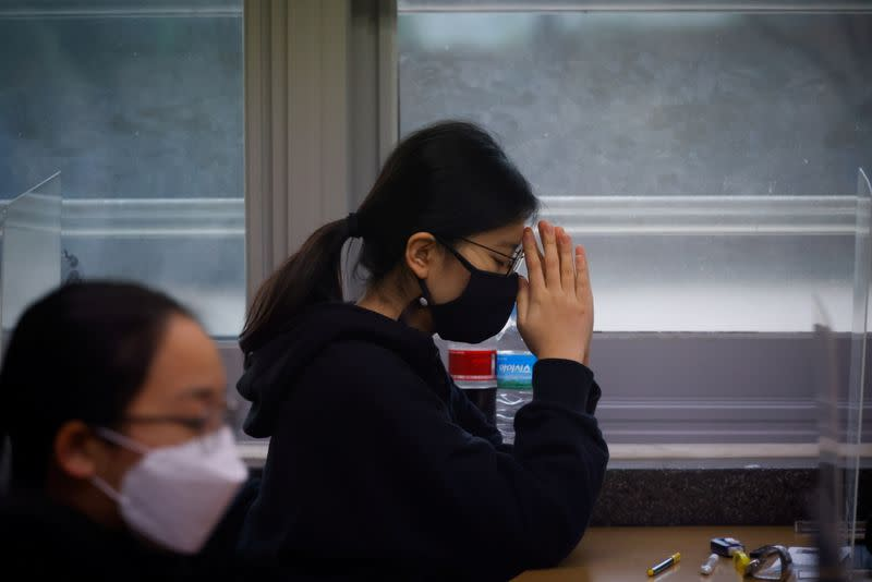 A student prays ahead of the annual college entrance examinations amid the coronavirus disease (COVID-19) pandemic at an exam hall in Seoul