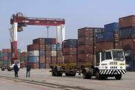 FILE - In this July 24, 2019, file photo, workers watch as a truck passes by stacks of shipping containers at a port in Yingkou in northeastern China's Liaoning Province. Shortages of power, computer chips and other parts, soaring shipping costs and shutdowns of factories to battle the pandemic are taking a toll on Asian economies. (AP Photo/Olivia Zhang, File)