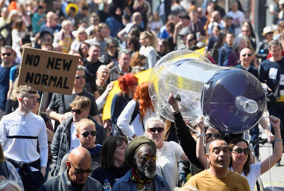 Demonstrators carry an inflatable syringe as they march through LondonREUTERS