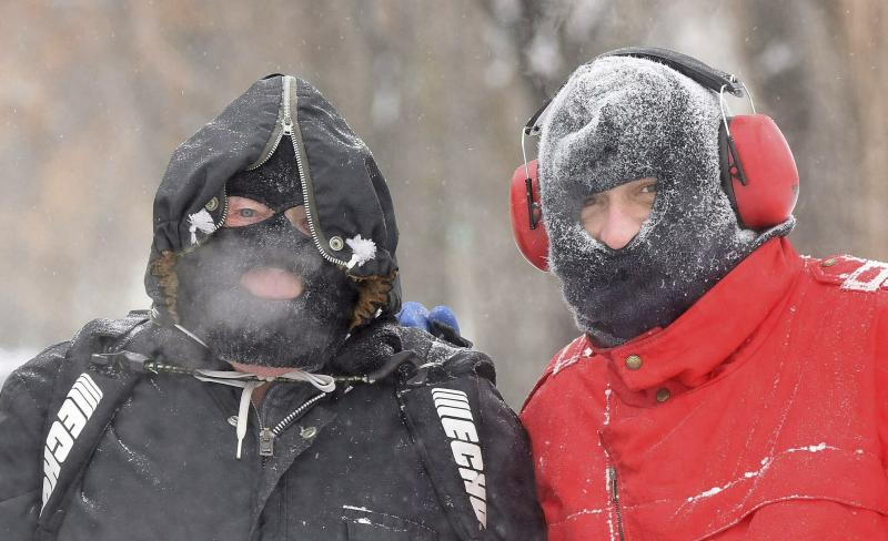 Father and son John, left, and Johnny Nagel were dressed for the cold temperatures on Friday while shoveling snow outside their north Bismarck, N.D., home Friday, Jan. 18, 2019,. (Tom Stromme/The Bismarck Tribune via AP)