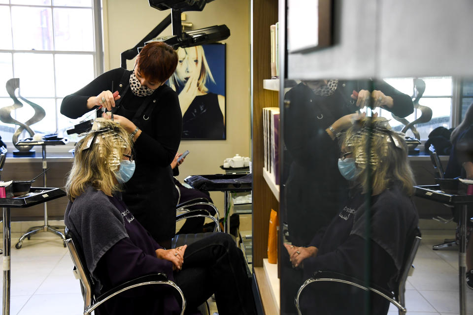 A hairdresser works with a client at Richard Ward Hair & MetroSpa in London, Wednesday, Nov. 4, 2020. Britain is preparing to join large swathes of Europe in a coronavirus lockdown designed to save its health care system from being overwhelmed. Pubs, along with restaurants, hairdressers and shops selling non-essential items will have to close Thursday until at least Dec. 2. (AP Photo/Alberto Pezzali)