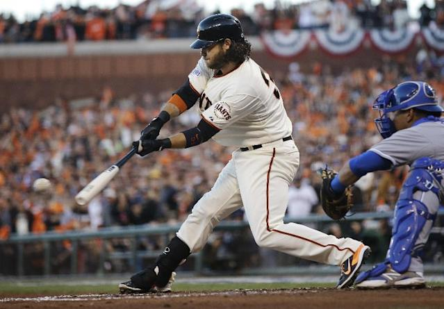 Kansas City Royals catcher Salvador Perez watches as San Francisco Giants Brandon Crawford hits an RBI ground out to score Hunter Pence during the second inning of Game 5 of baseball's World Series against the Kansas City Royals Sunday, Oct. 26, 2014, in San Francisco. (AP Photo/Matt Slocum)
