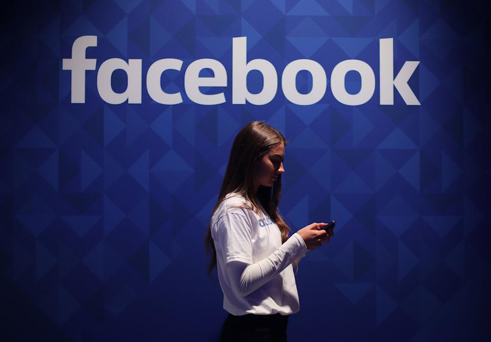 File photo dated 03/11/15 of a woman using her phone under a logo of Facebook. The prevalence of hate speech on Facebook is decreasing, the social media giant has claimed, as it published its latest report on how the site enforces its rules. The firm said hate speech was now appearing in around five posts per 10,000, down from between five and six per 10,000 in the first three months of this year. Issue date: Wednesday August 18, 2021.