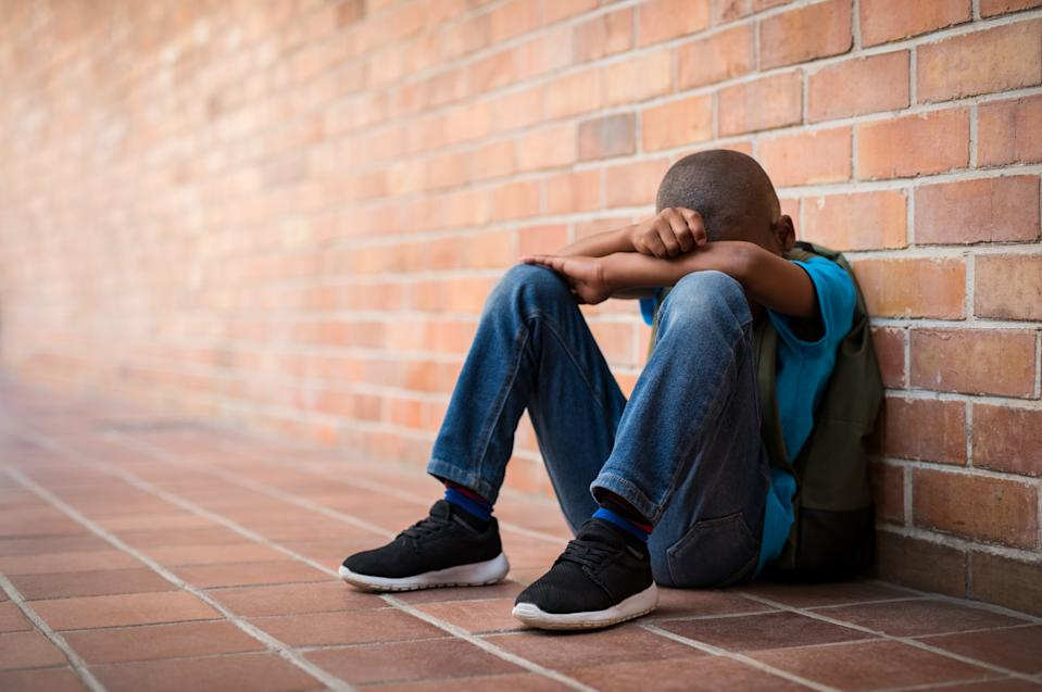 Young boy sitting alone with sad feeling at school. Depressed african child abandoned in a corridor and leaning against brick wall. Bullying, discrimination and racism concept at school with copy space.
