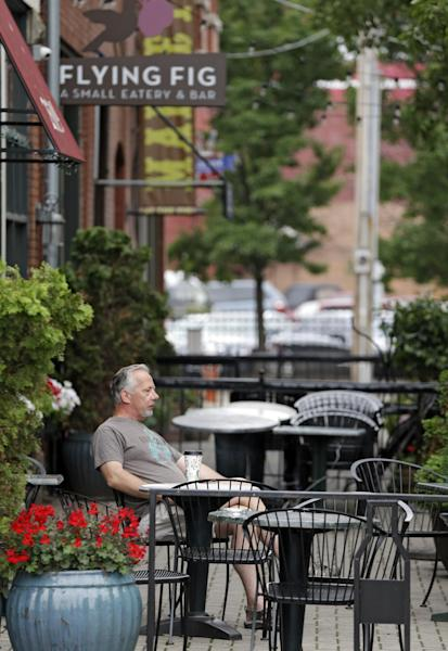 In this July 1, 2013 photo, Paul Nasvytis enjoys his morning coffee at Koffie Cafe across from the Great Lakes Brewing Co. in Cleveland's Ohio City neighborhood. In rundown urban neighborhoods across the country, craft breweries like Great Lakes helped transform the neighborhoods around them, drawing young new residents and other small businesses. (AP Photo/Mark Duncan)
