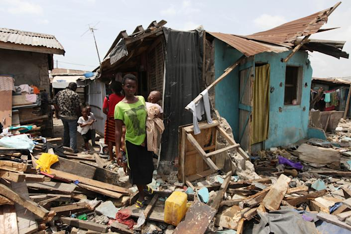 In this image taken Thursday Feb. 28, 2013, a woman carries her child stand in front of a partly demolished house at Ijora Badia slum in Lagos, Nigeria,. The bulldozers arrived at dawn to this neighborhood of shanty homes and concrete buildings in Nigeria's largest city, followed by police officers in riot gear carrying Kalashnikov assault rifles. The police banged on doors, corralling the thousands who live in Ijora-Badia off to the side as the bulldozers' blades tore through scrap-lumber walls, its track grinding the possessions inside into the black murk of swamp beneath it. It left behind only a field of debris that children days later picked through, their small hands dodging exposed rusty nails to pull away anything of value left behind. (AP Photo/Sunday Alamba)