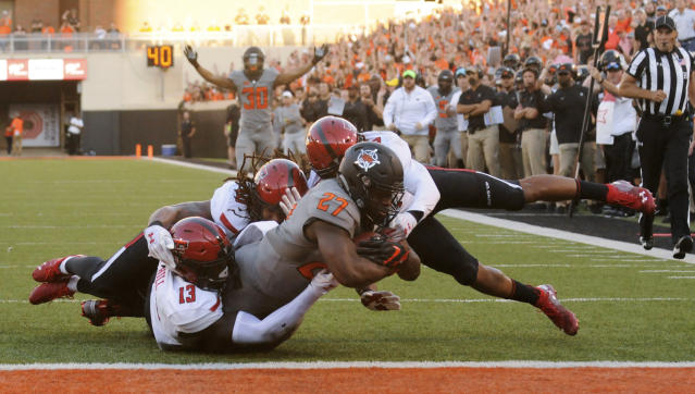 Oklahoma State running back J.D. King (27) scores a touchdown while being tackled by Texas Tech linebackers Kolin Hill, left, and Dakota Allen, back center, and defensive back John Bonney during the first half of an NCAA college football game in Stillwater, Okla., Saturday, Sept. 22, 2018. (AP Photo/Brody Schmidt)