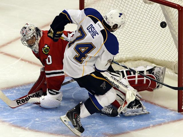 St. Louis Blues' T.J. Oshie (74) scores against Chicago Blackhawks goalie Corey Crawford (50) during a shootout in an NHL hockey game in Chicago, Thursday, Oct. 17, 2013. The Blues won 3-2. (AP Photo/Nam Y. Huh)