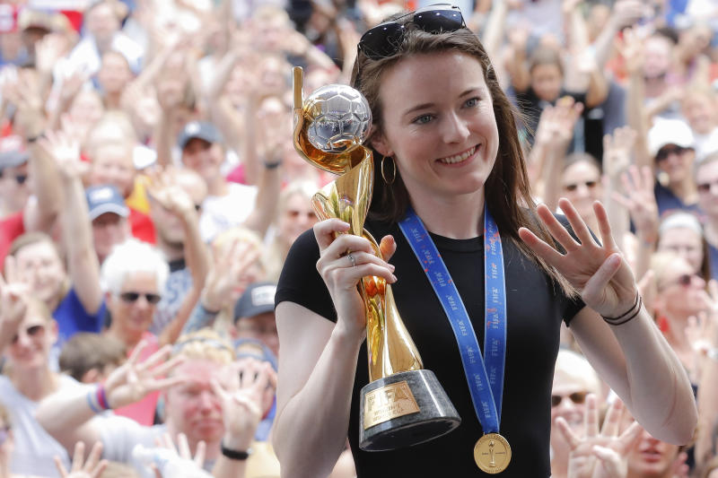 Rose Lavelle with the World Cup trophy holding four fingers.