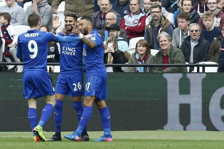 Leicester City's midfielder Riyad Mahrez (C) celebrates with striker Jamie Vardy (L) and defender Danny Simpson after scoring during the English Premier League football match against West Ham United March 18, 2017