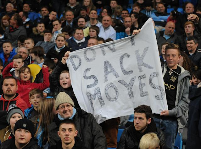 Manchester City supporters display a banner with reference to Manchester United manager David Moyes, during the English Premier League soccer match between Manchester City and West Bromwich at the Etihad Stadium, Manchester, England, Monday, April 21, 2014. (AP Photo/Rui Vieira)