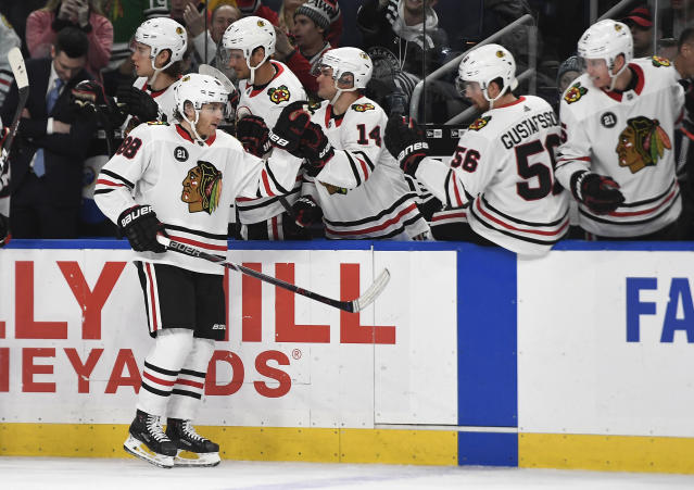 Chicago Blackhawks right wing Patrick Kane is congratulated by teammates after scoring during the third period of the team's NHL hockey game against the Buffalo Sabres in Buffalo, N.Y., Friday, Feb. 1, 2019. Chicago won 7-3. (AP Photo/Adrian Kraus)