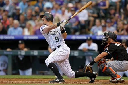 Jun 22, 2018; Denver, CO, USA; Colorado Rockies second baseman DJ LeMahieu (9) hits an RBI sacrifice fly against the Miami Marlins in the fourth inning at Coors Field. Mandatory Credit: Aaron Doster-USA TODAY Sports