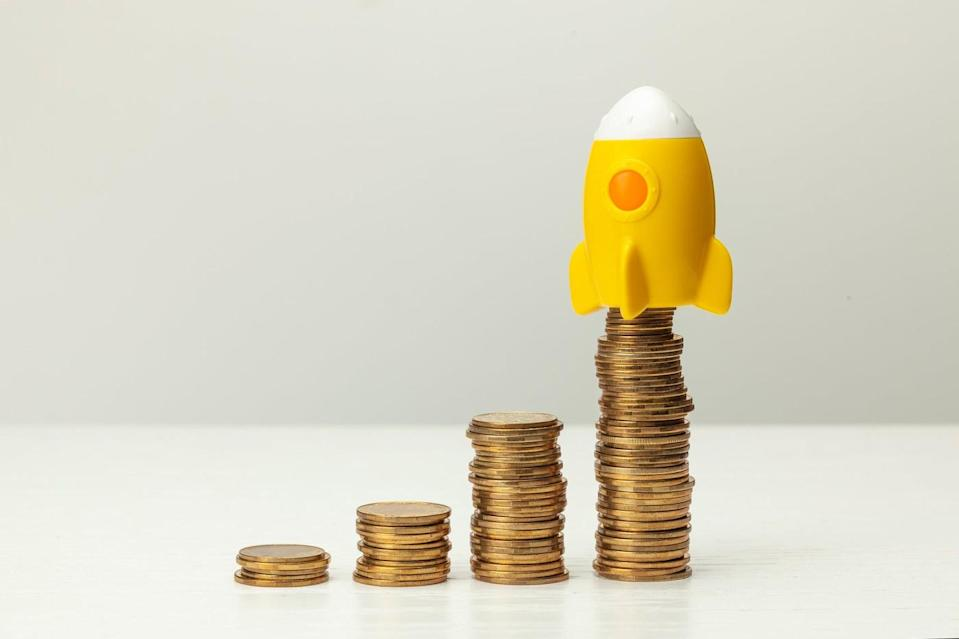 Stacks of coins and a miniature rocket on the tallest stack.