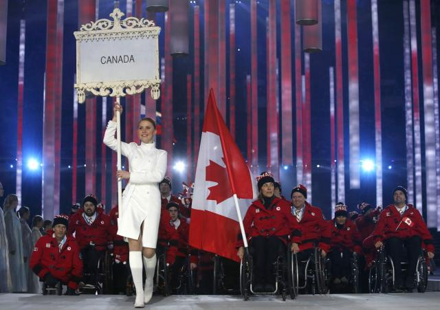 Canada's flag-bearer Sonja Gaudet (C), leads his country's contingent during the opening ceremony of the 2014 Paralympic Winter Games in Sochi, March 7, 2014. REUTERS/Alexander Demianchuk (RUSSIA - Tags: OLYMPICS SPORT)
