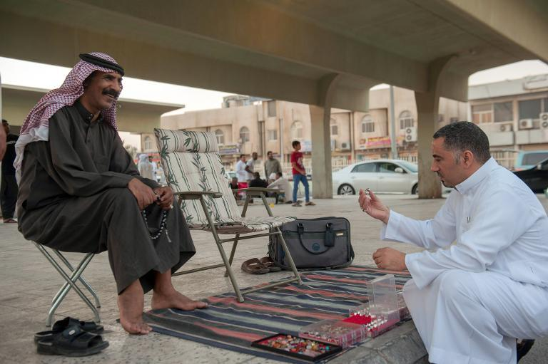 A Saudi street vendor speaks with a resident in the mainly Shiite town of Qatif, November 11, 2014. Solidarity gestures by Sunni leaders are helping to bridge a divide with the minority