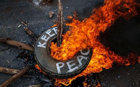 Supporters of the opposition leader Raila Odinga burn a tyre - Credit: EPA