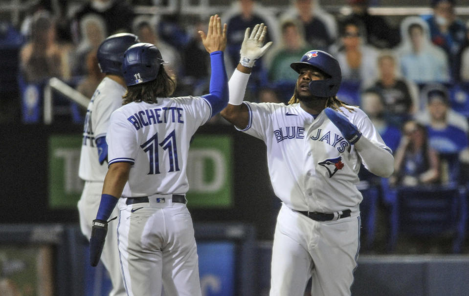 Toronto Blue Jays' Bo Bichette (11) and Vladimir Guerrero Jr. celebrate after scoring on Randal Grichuk's three-run double off Los Angeles Angels' Jose Quintana during the second inning of a baseball game Saturday, April 10, 2021, in Dunedin, Fla. (AP Photo/Steve Nesius)