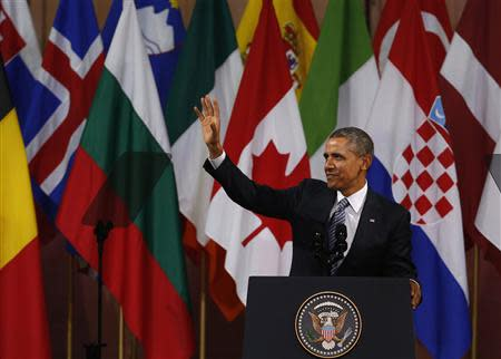 U.S. President Obama waves after his speech at the Bozar concert hall in Brussels