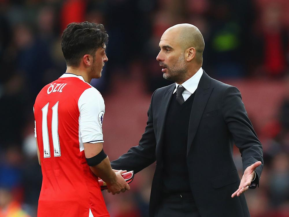 Pep Guardiola speaks to Mesut Ozil after the final whistle: Getty