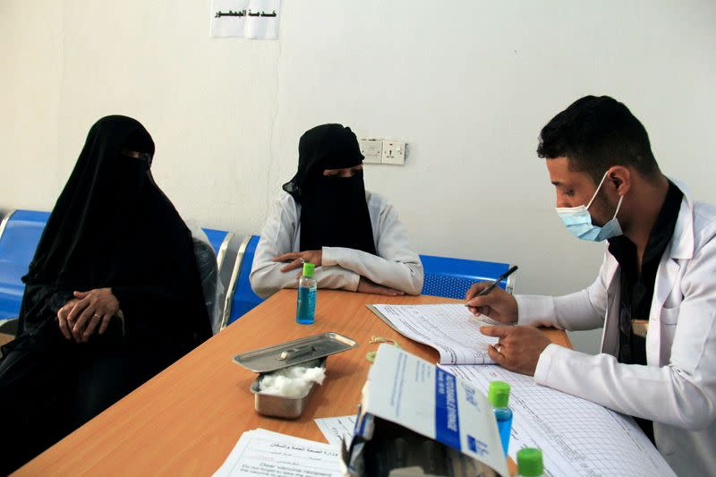 FILE PHOTO: A medical staffer writes down details of a woman who received the AstraZeneca vaccine against COVID-19 at a medical center in Taiz, Yemen