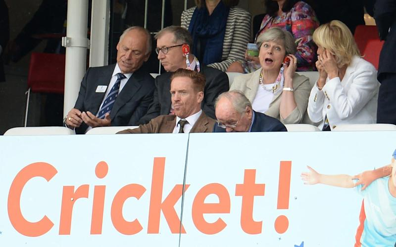 Theresa May reacts as she adjusts her radio during the third cricket test between England and the West Indies last September - 2017 Philip Brown