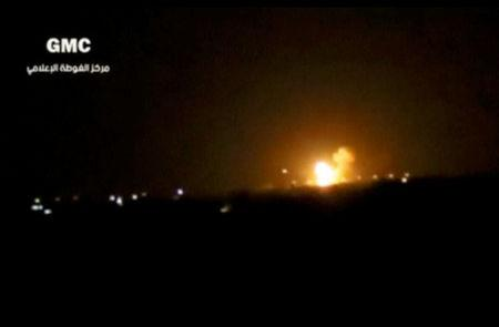 A still image taken from a video posted to a social media website and said to be shot on April 27, 2017, shows explosions and rising flames amid lights in distance, said to be shot in Damascus