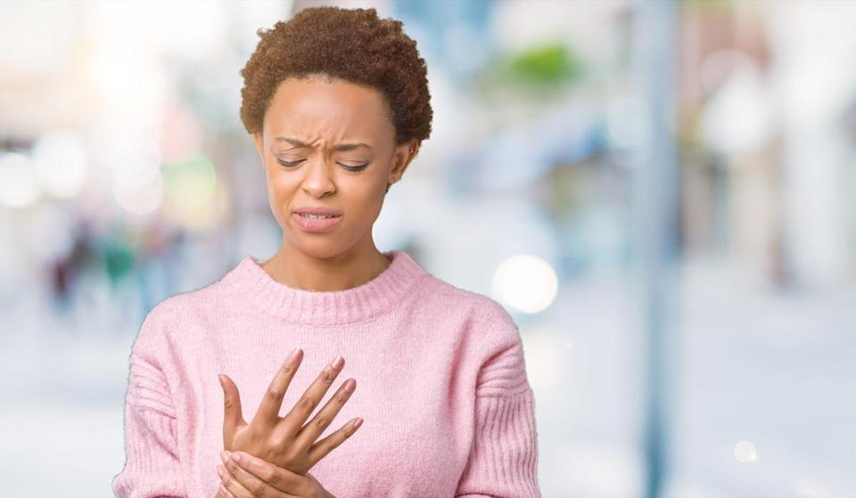young african american woman over isolated background Suffering pain on hands and fingers, arthritis inflammation