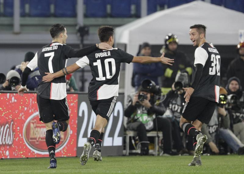 Juventus' Cristiano Ronaldo, left, celebrates with teammates Juventus' Paulo Dybala, centre, and Juventus' Rodrigo Bentancur after scoring his side's opening goal during the Italian Serie A soccer match between Lazio and Juventus at Rome's Olympic stadium, in Rome, Italy, Saturday, Dec. 7, 2019. (AP Photo/Gregorio Borgia)