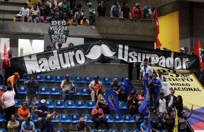 """Government opponents display a banner that reads in Spanish """"Maduro usurper,"""" referring to Vice President Nicolas Maduro at an event commemorating the 1958 fall of Gen. Marcos Perez Jimenez, Venezuela's last dictator, in Caracas, Venezuela, Wednesday, Jan. 23, 2013. Some government adversaries have likened President Hugo Chavez to Perez Jimenez, saying both attempted to silence the news media, used the judiciary to jail adversaries and infringed on freedoms. (AP Photo/Fernando Llano)"""