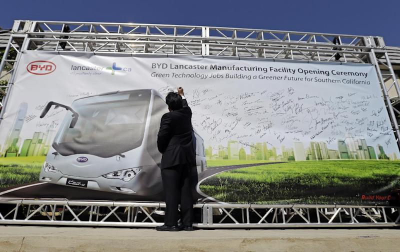 A visitor writes on a banner during a news conference announcing the opening of an electric bus manufacturing plant by Chinese-owned vehicle manufacturer BYD Automotive in Lancaster, Calif. on Wednesday, May 1, 2013. In April, the Long Beach Transit Authority awarded BYD a $12.1 million contract for the zero-emission buses, a company statement said. (AP Photo/Reed Saxon)