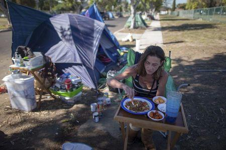 Stacie McDonough, 51, eats lunch by her tent in a homeless RV and tent encampment near LAX airport in Los Angeles, California, United States, October 26, 2015.  REUTERS/Lucy Nicholson