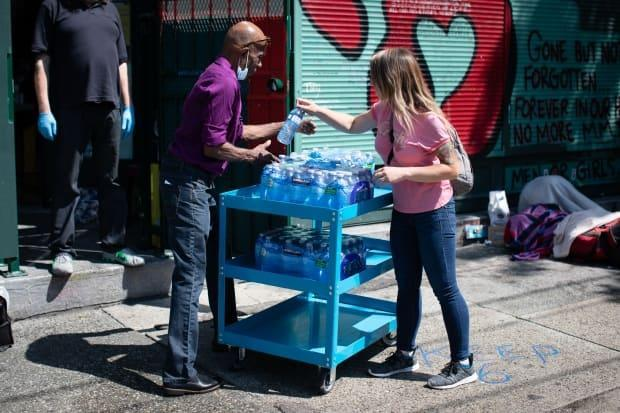 Water is handed out near an overdose prevention site in Vancouver's Downtown Eastside on Tuesday. Municipalities like the City of Vancouver are updating their heat response plans after criticism. (Maggie MacPherson/CBC - image credit)